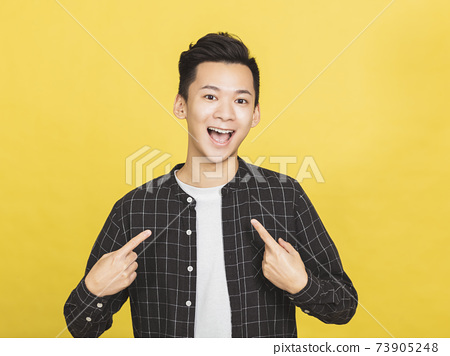 young man smiling and pointing at himself 73905248