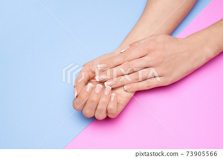 Beautiful Female Hands with French manicure over colorful paper background 73905566