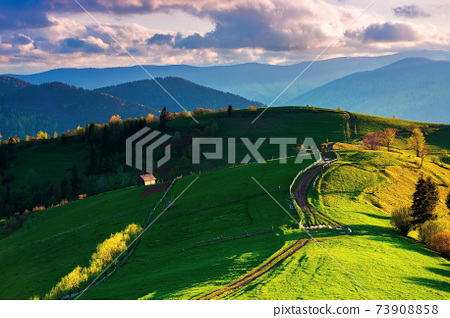 path winding through rural field on hill. wooden fence and trees along the way. fluffy clouds above the distant ridge in evening. wonderful countryside landscape in spring at sunset 73908858