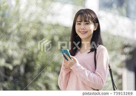 看與智能手機的少婦照相機 73913269