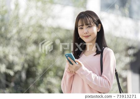 看與智能手機的少婦照相機 73913271