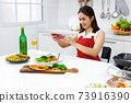 Asian woman in red apron taking a picture of food she make with mobile phone. Concept woman preparing meals at home. 73916390