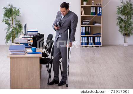 Young leg injured male employee working in the office 73917005