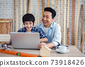 Asian father and son using laptop computer together in carpentry workshop. Concept family doing hobby at home. 73918426