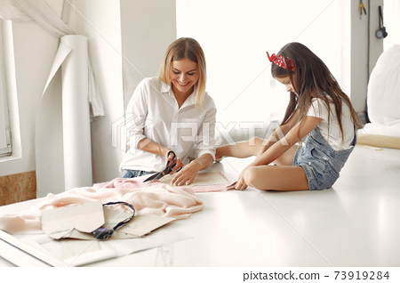 Mother with little daughter measure the fabric for sewing 73919284