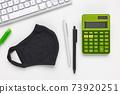 Mask, keyboard and calculator. Tax return concept 73920251