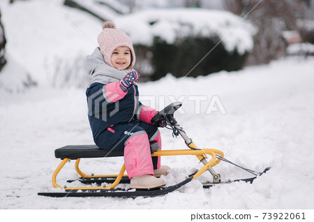 Little girl enjoy a sleigh ride. Kid sledding. Kids sled in park in winter. Outdoor fun for family Christmas vacation 73922061