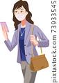 一名婦女戴著口罩,檢查她的智能手機上的位置並前往營業地點 73933545