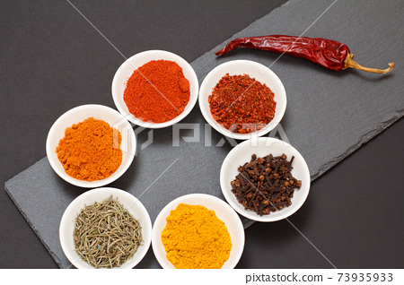 Various ground spices and herbs on stone cutting board. 73935933