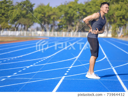 Young fitness man holding his sports injury, muscle painful during training 73964432