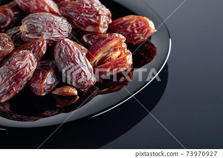 Dried sweet dates on a black plate. 73970927