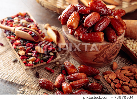Dried fruits, various nuts and seeds on a wooden table. 73970934