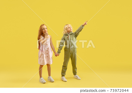 Childhood and dream about big and famous future. Boy and girl isolated on yellow studio background 73972044