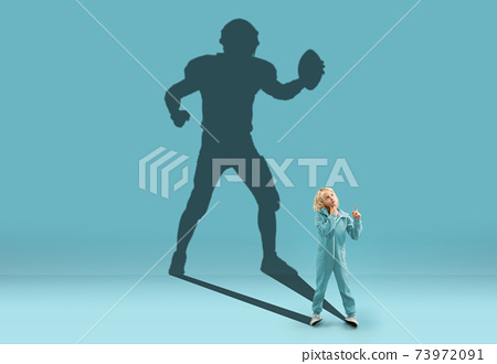 Childhood and dream about big and famous future. Conceptual image with boy and shadow of fit male american football player on blue background 73972091