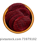 Cooked beetroot slices in a wooden bowl. Boiled sliced red beets also known as table, garden, dinner or golden beets. Beta vulgaris. Taproots. Food and food coloring. Close-up, from above, food photo. 73979102