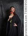 Woman in black dress with red rose 73983956