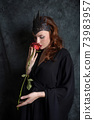 Woman in black dress sniffs red rose 73983957