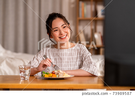 年輕女子在晚上吃飯時看電視 73989587