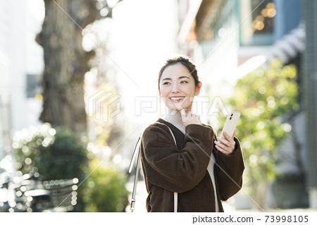 戶外的年輕女子智能手機搜索 73998105