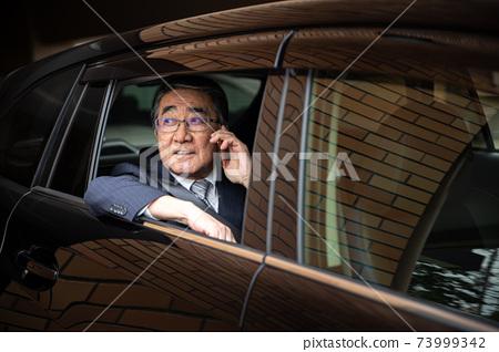 在一輛車的男性智能手機 73999342