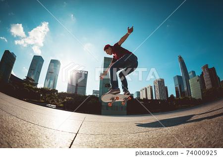 Skateboarder skateboarding at sunrise park 74000925