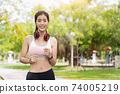 Asian women wear costumes for exercise and jacket running in the park,Asian women are practicing to run a marathon or cardio to lose weight Sport and healthy concept with park background. 74005219
