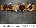 Brown unroasted and dark roasted coffee beans in coffee cup with scoops setup on dark stone background. 74012131