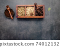 Green and brown unroasted and dark roasted coffee beans in wooden box with scoops setup on dark concrete background. 74012132