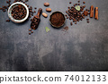 Roasted coffee beans with coffee powder and flavourful ingredients for make tasty coffee setup on dark stone background. 74012133