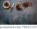 Roasted coffee beans with coffee powder and flavourful ingredients for make tasty coffee setup on dark stone background. 74012134