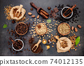 Coffee background with various of roasted coffee beans and flavourful ingredients for make tasty coffee setup on dark stone background. 74012135