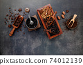 Various of roasted coffee beans in wooden box with manual coffee grinder setup on dark stone background. 74012139