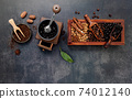 Various of roasted coffee beans in wooden box with manual coffee grinder setup on dark stone background. 74012140