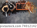 Various of roasted coffee beans in wooden box with manual coffee grinder setup on dark stone background. 74012142