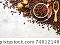 Background of dark roasted coffee beans and capsules with scoops setup on white concrete background with copy space. 74012146