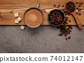 Roasted coffee beans with coffee cup setup on dark stone background. 74012147