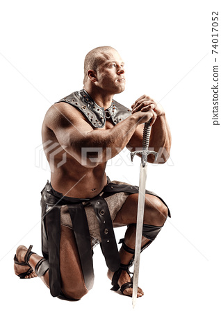 Severe barbarian in leather costume with sword. Portrait of balded muscular gladiator. Studio shot. Isolated on white background 74017052