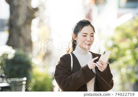 尋找在她的智能手機上一個年輕女子目的地 74022759