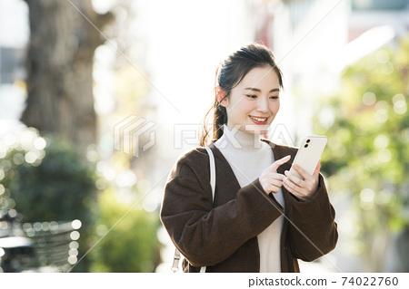 尋找在她的智能手機上一個年輕女子目的地 74022760