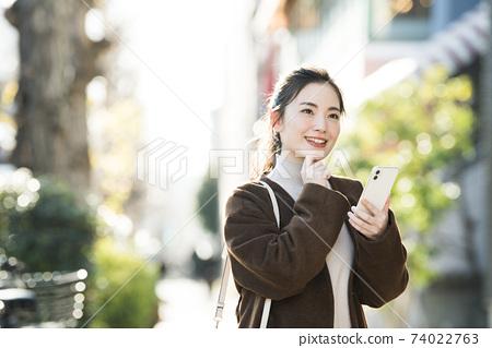 尋找在她的智能手機上一個年輕女子目的地 74022763