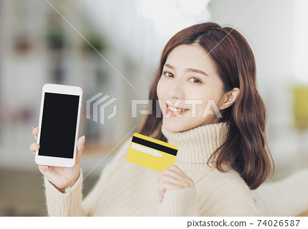 young woman shopping online using mobile phone and credit card 74026587