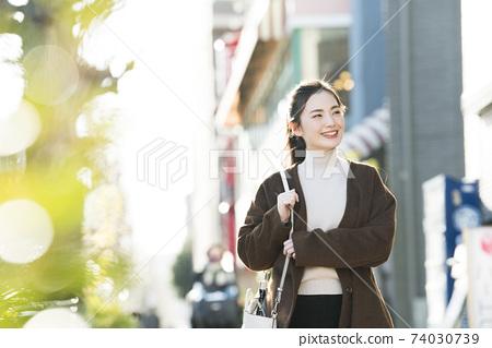 거리를 걷는 젊은 여성 74030739