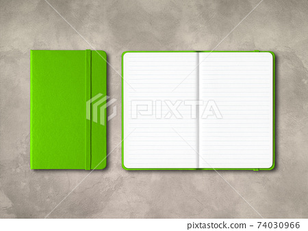 Green closed and open lined notebooks on concrete background 74030966