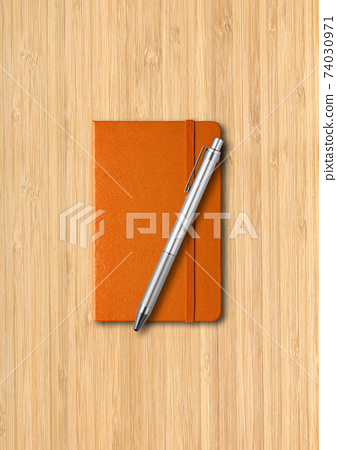 Orange closed notebook with a pen on wooden background 74030971