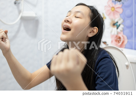 Defecation and urination,Happy asian people sitting on the toilet,emotions and gestures facial expressions happy,defecating in the bathroom,child girl with relief and satisfaction after constipation 74031911