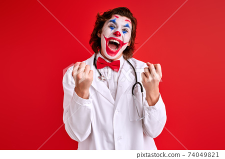artistic Clown doctor with colourful make-up have fun 74049821