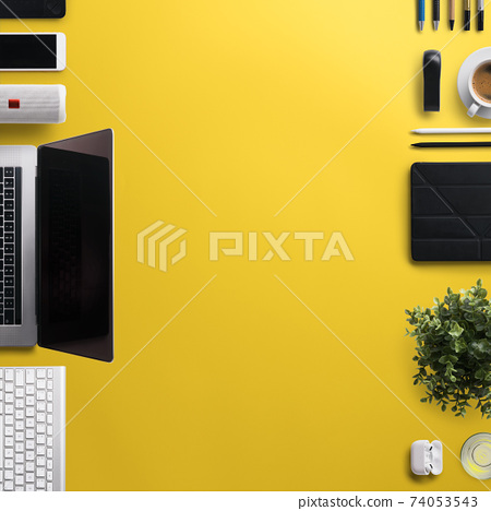 Flat lay top view office desk working space with laptop and office supplies on yellow background. 74053543