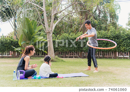 mother and child daughter practicing doing yoga exercises outdoors cheer father playing with hula hoops 74061060