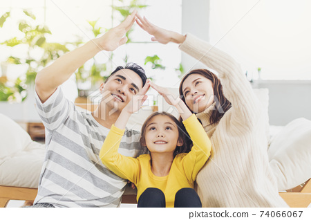 Happy asian family forming house roof with their hands at home 74066067