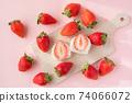一護大福的橫斷面在木板上。環繞著它的草莓的鳥瞰圖。白豆沙粉紅色背景 74066072
